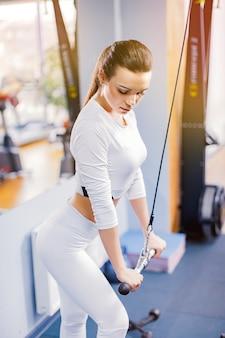Geeigneter frauentrainings-trizeps, der gewichte in der turnhalle anhebt