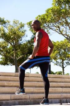 Geeigneter junger afrikanischer mann, der auf schritten am park steht