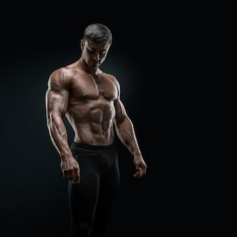 Geeigneter junger bodybuilder, der über schwarzem hintergrund aufwirft
