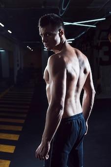 Geeigneter junger mann, der im fitness-club steht