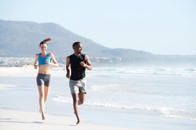 Geeigneter junger mann und frau, die entlang den strand laufen