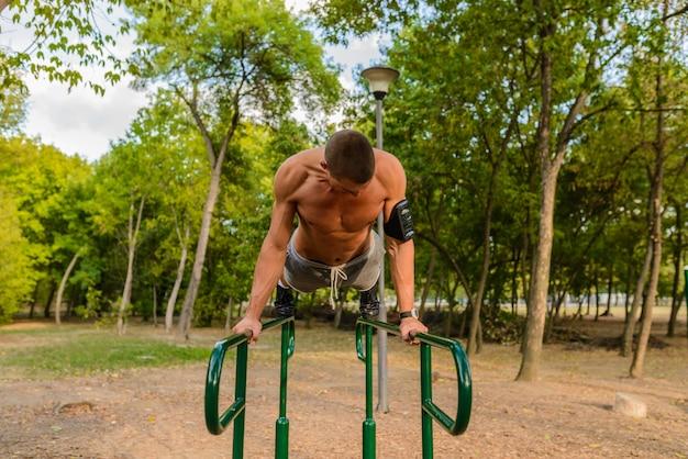 Geeigneter mann, der am park trainiert und ein gesundes leben führt