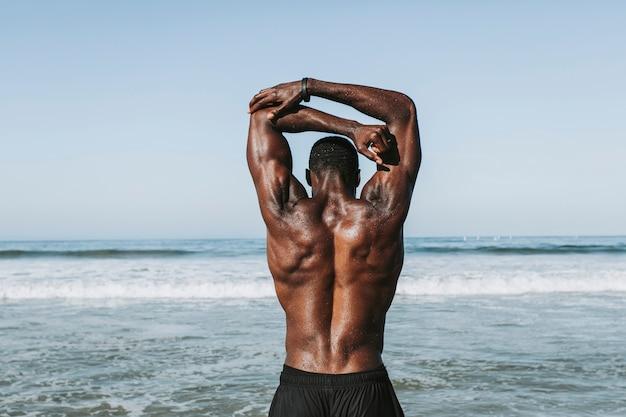 Geeigneter mann, der am strand ausdehnt