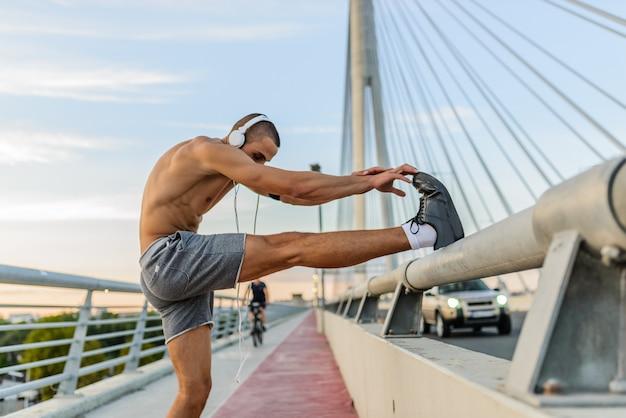 Geeigneter mann, der auf der brücke trainiert und ein gesundes leben führt