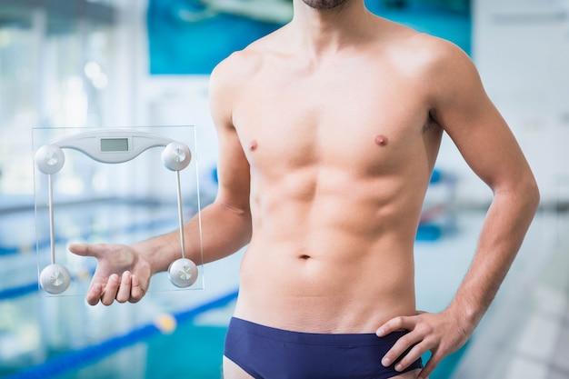 Geeigneter mann, der eine gewichtsskala am pool hält
