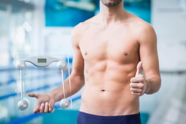 Geeigneter mann, der eine gewichtsskala mit den daumen oben am pool hält