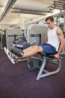 Geeigneter mann, der gewichtsmaschine für beine verwendet