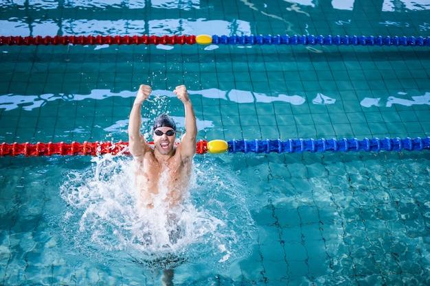 Geeigneter mann, der im pool triumphiert