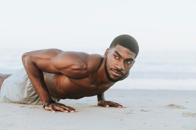 Geeigneter mann, der liegestütze im sand tut
