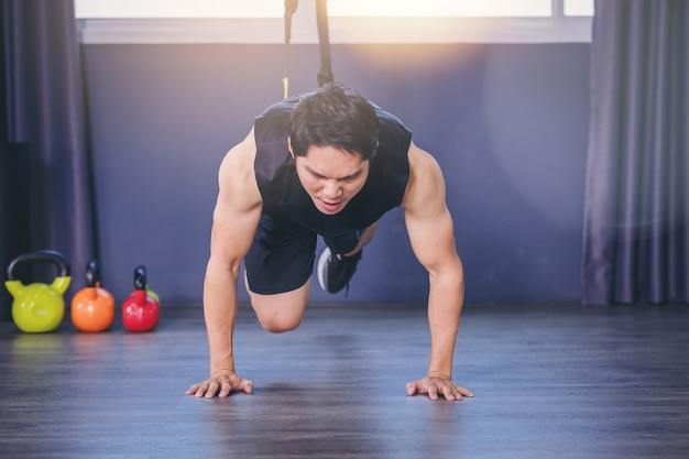 Geeigneter mann, der plankenübung für hinteren dorn tut, indem sie ups mit seileignungsgurten in der turnhalle drücken