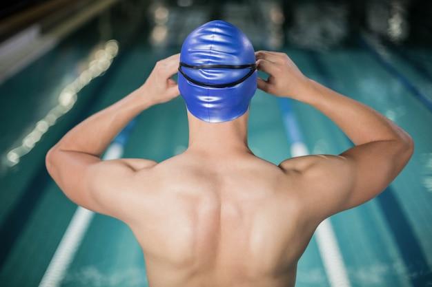 Geeigneter mann, der seine schutzbrillen am pool justiert