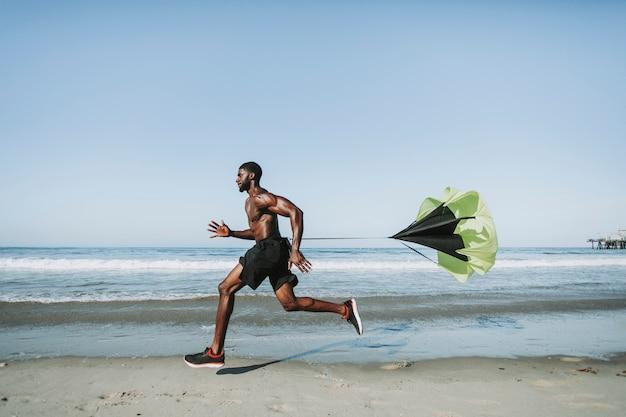 Geeigneter mann mit einem laufenden fallschirm am strand