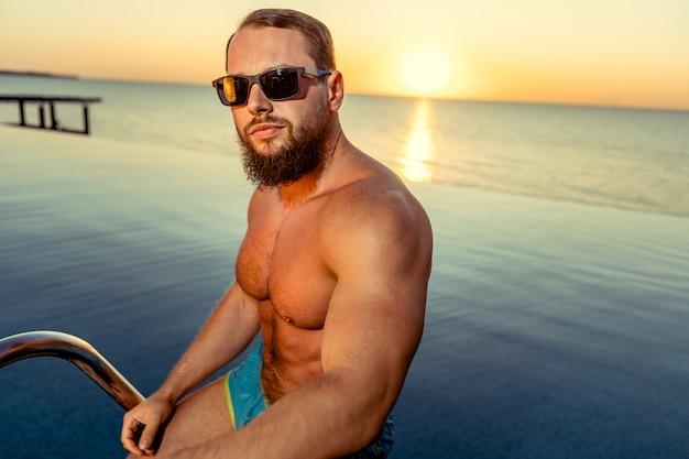 Geeigneter mannbodybuilder, der aus pool herauskommt