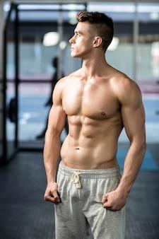 Geeigneter muskulöser mann, der shirtlessb an der turnhalle aufwirft