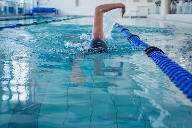 Geeigneter schwimmer, der den vorderen anschlag im swimmingpool tut
