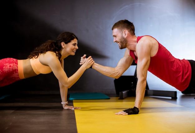Geeigneter sportiver mann und frau, die plankenkernübung tut