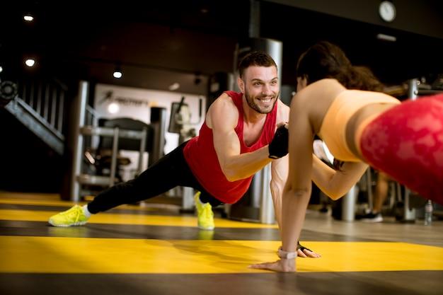Geeigneter sportlicher mann und frau, die plankenkernübung tut