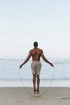 Geeigneter springendes seil des mannes am strand
