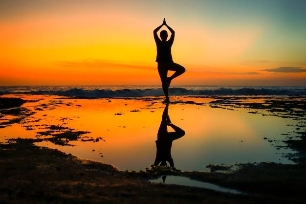 Geeigneter stand des jungen mannes und übt sonnengrußyoga auf dem strand bei sonnenuntergang.