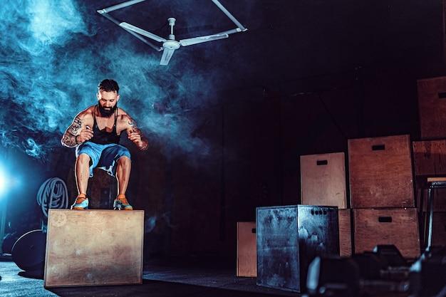 Geeigneter tätowierter bärtiger mann, der als teil des übungsprogramms auf eine schachtel springt. mann, der kastensprung in die turnhalle tut. athlet führt kastensprünge durch
