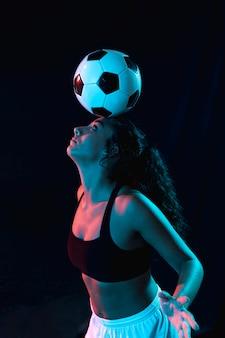 Geeignetes mädchen des erwachsenen, das tricks mit ball tut