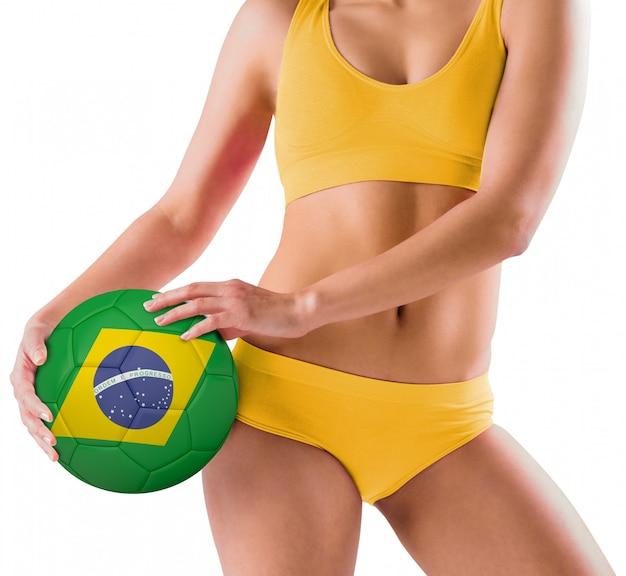 Geeignetes mädchen im gelben bikini, der brasilien-fußball hält