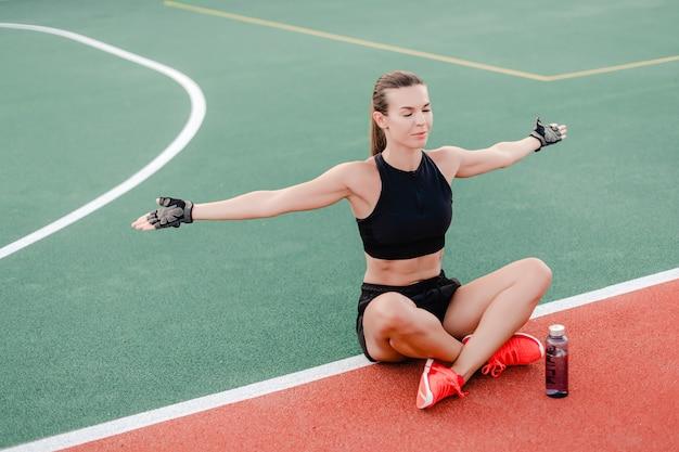 Geeignetes trinkwasser der sportlichen frau von der flasche auf stadion während des eignungstrainings