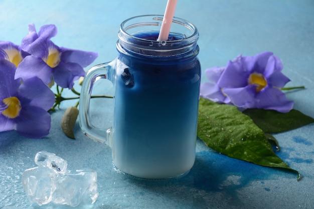 Geeister schmetterlingserbsenlatte. gesundes sommerkaltgetränk, gefrorener organischer blauer und violetter schmetterlingserbsenblütentee