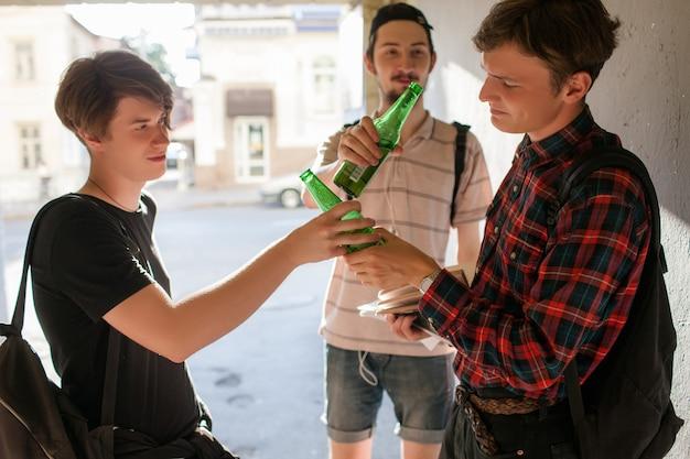 Geek-junge gerät unter schlechten einfluss. konzept der schlechten gewohnheiten der alkoholsucht im teenageralter. moderner urbaner jugend-lifestyle