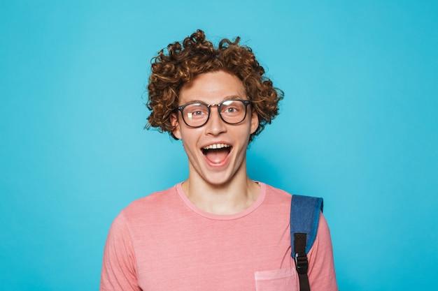 Geek kerl mit dem lockigen haar, das brille und rucksack trägt, der in die kamera lächelt