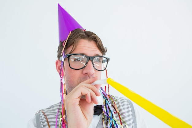Geeky hippie, der einen partyhut mit schlagparteihorn trägt