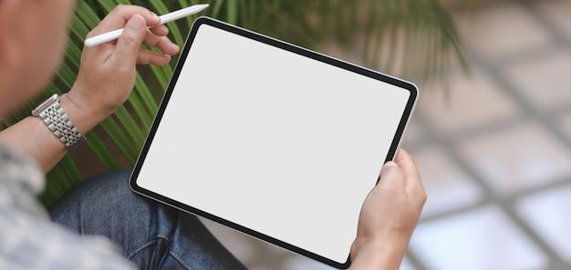 Geerntet vom geschäftsmann unter verwendung der digitalen tablette des leeren bildschirms beim arbeiten an seinem projekt