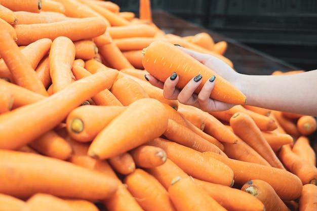 Geerntet von den kaufenden früchten der jungen frau am markt des landwirts