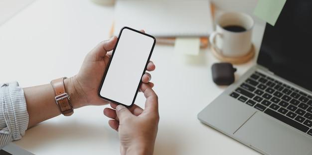 Geerntete ansicht der mannhand smartphone des leeren bildschirms halten