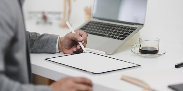 Geerntete ansicht des berufsgeschäftsmannes arbeitend an seinem projekt beim schreiben auf tablette des leeren bildschirms