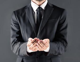 Geerntete Ansicht des Geschäftsmannes in der Klage mit den offenen Händen, lokalisiert auf Grau