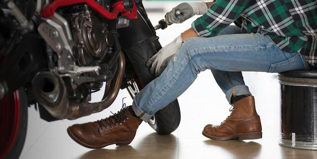Geerntete ansicht des motorradmechanikers unter verwendung eines schlüssels und eines sockels auf einem motorrad