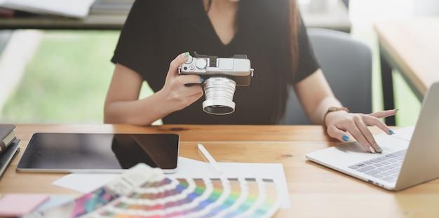 Geerntete ansicht des weiblichen grafikdesigners arbeitend an ihrem projekt