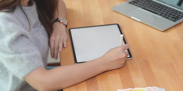Geerntete ansicht eines jungen weiblichen freiberuflers, der ihre idee auf tablette schreibt