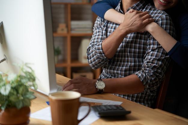 Geerntete frau, die ihren unerkennbaren ehemann mit einer umarmung stützt