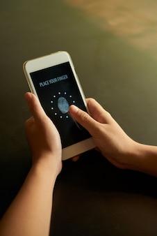 Geerntete hände, die fingerabdruck auf smartphone scannen