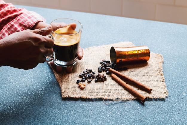 Geerntete hand, die einen tasse kaffee mit bestandteil hält.