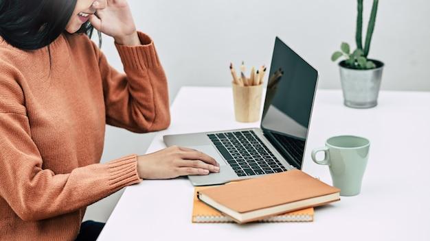 Geerntete kreative frau des schusses, die mit computerlaptop auf tabelle arbeitet.