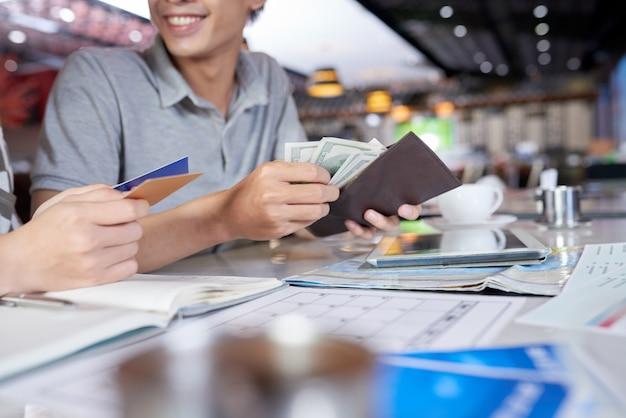 Geerntete leute, die ihre geldbörse auf geld und bankkarte überprüfen