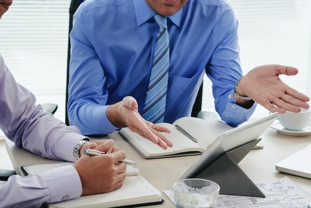 Geerntete männer, die jahresbericht unter verwendung der digitalen tablette besprechen