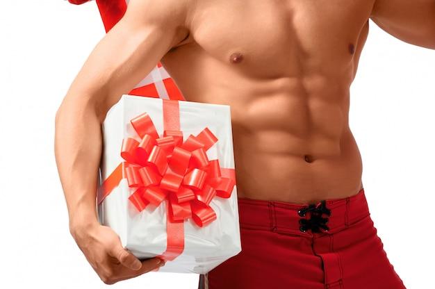 Geerntete nahaufnahme eines sexy hemdlosen mannes, der großes geschenk hält.