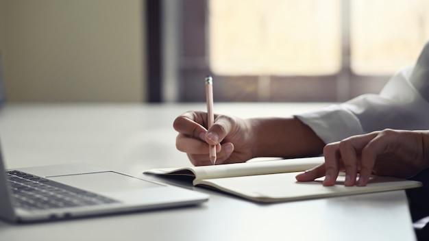 Geerntete schussfrau, die an tabelle mit dem schreiben auf notizbuchpapier arbeitet.
