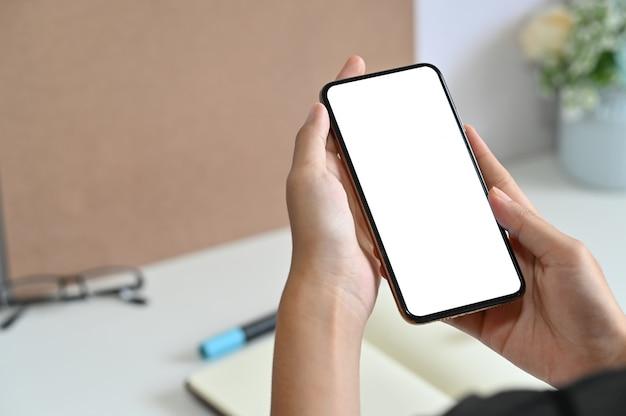 Geerntete schussfrau, die modell smartphone auf schreibtisch verwendet