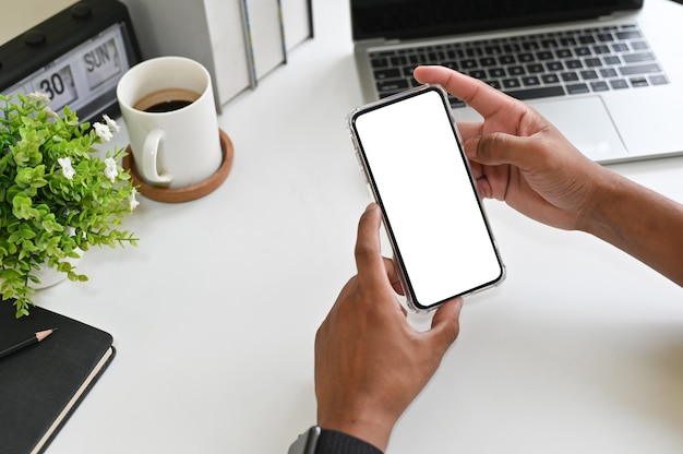 Geerntete schusshände unter verwendung des modells smartphone auf schreibtisch mit beschneidungspfad.