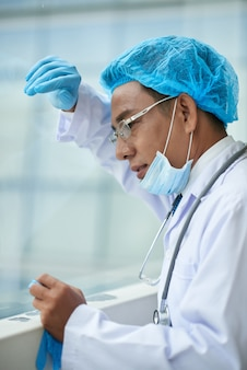 Geerntete seitenansicht des chirurgen ermüdete nach der chirurgie, die am fenster sich lehnt